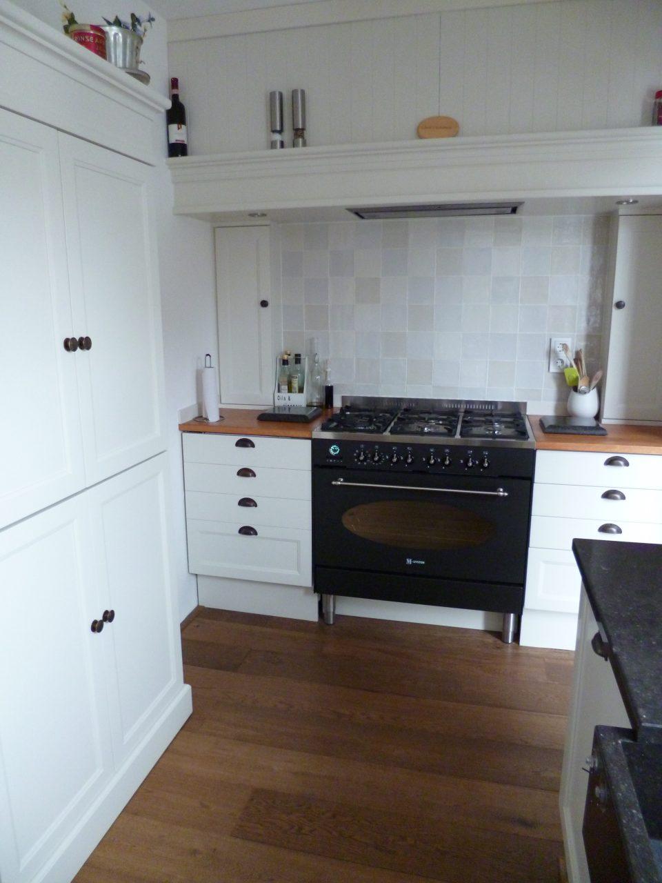Deze landelijke keuken is modulair opgebouwd. Het werkblad is Belgisch hardsteen gezoet in combinatie met een werkblad van gestoomd beuken, afgewerkt met corcol olie.
