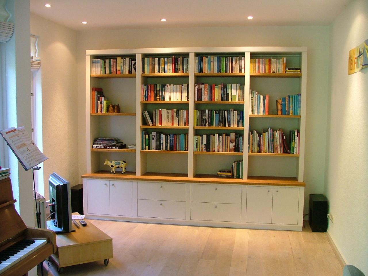 Witte boekenkast, op maat gemaakt met kastjes.
