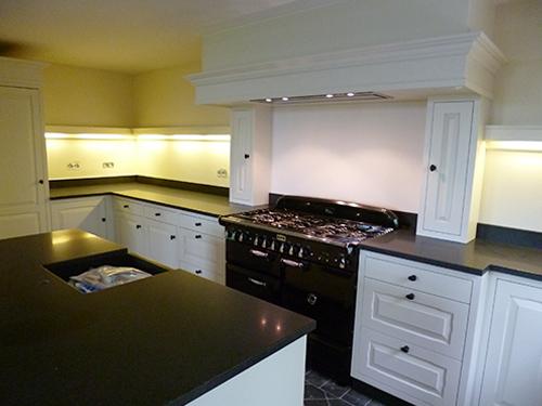 Moderne maatwerk keuken van wit hout met een zwart keukenblad.