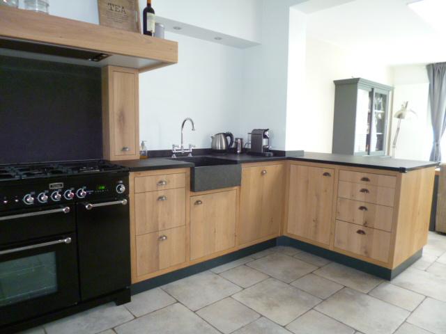 Keuken met landelijk design, met kasten in houtkleur en een zwart keukenblad.